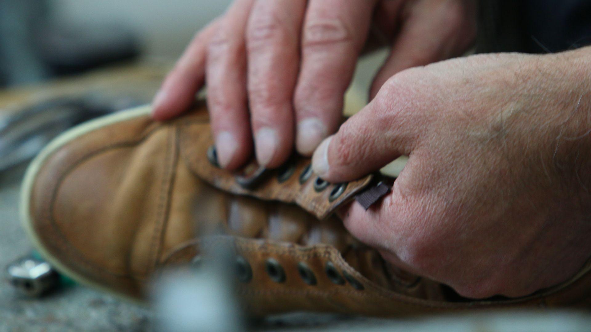 Hände reparieren Schuhe